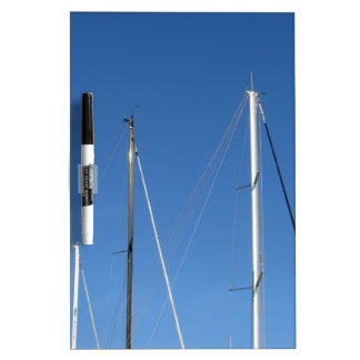 Sailboat masts in the marina against a blue sky dry erase whiteboards