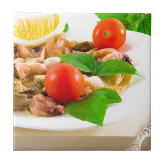 Salad of blanched pieces of seafood on a plate tile