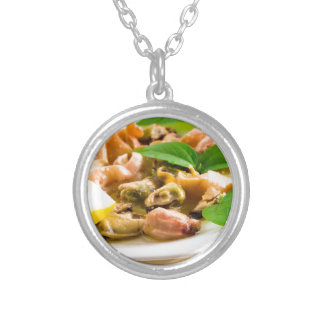 Salad of blanched seafood on a white plate silver plated necklace