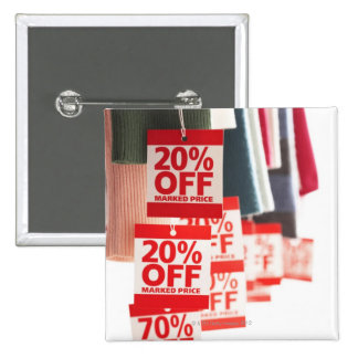 Sale tags attached to hanging clothes, close-up 15 cm square badge