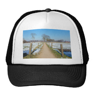 Sandpath between snowy meadows in dutch winter cap