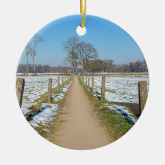 Sandpath between snowy meadows in dutch winter ceramic ornament