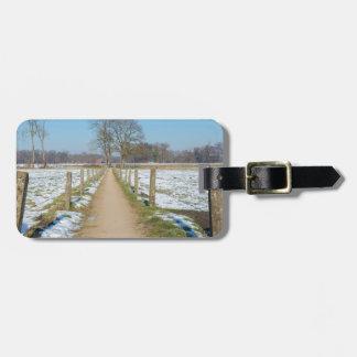Sandpath between snowy meadows in dutch winter luggage tag