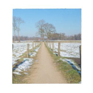 Sandpath between snowy meadows in dutch winter notepad