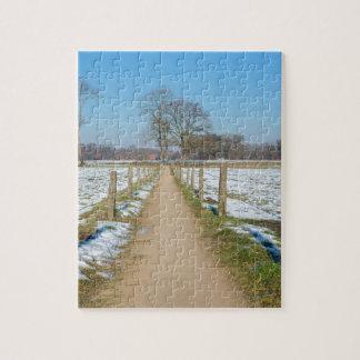 Sandpath between snowy meadows in dutch winter puzzle