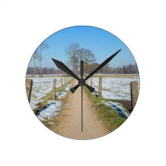 Sandpath between snowy meadows in dutch winter round clock