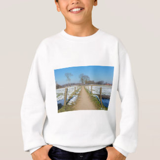 Sandpath between snowy meadows in dutch winter sweatshirt