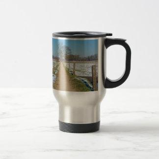 Sandpath between snowy meadows in dutch winter travel mug