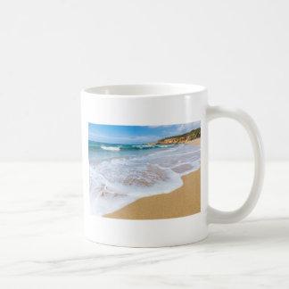 Sandy beach sea waves and mountain at coast coffee mug