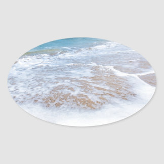 Sandy beach sea waves and mountain at coast oval sticker