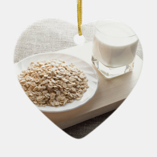 Saucer of cereal and a glass of milk in the backli ceramic heart decoration