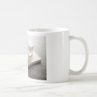 Saucer of cereal and a glass of milk in the backli coffee mug