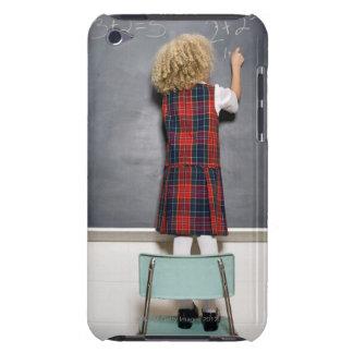 School girl (6-7) writing on blackboard, iPod touch case