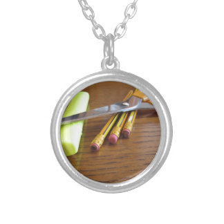 School office supplies on wooden table silver plated necklace