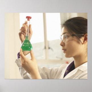 Scientist examining liquid in beaker posters