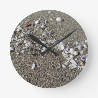 Seashells on sand. Summer beach background Round Clock