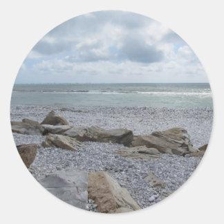 Seashore of beach with sailboats on the horizon classic round sticker