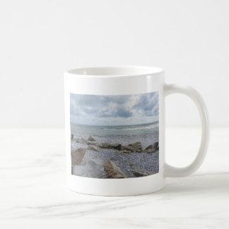 Seashore of beach with sailboats on the horizon coffee mug