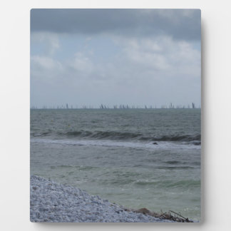 Seashore of beach with sailboats on the horizon plaque