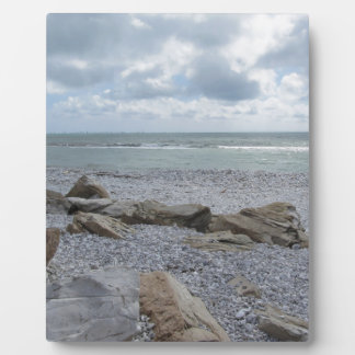 Seashore of beach with sailboats on the horizon plaques