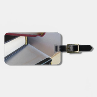 Second hand books with blank pages on a table luggage tag