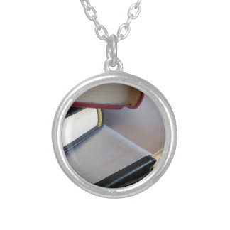 Second hand books with blank pages on a table silver plated necklace