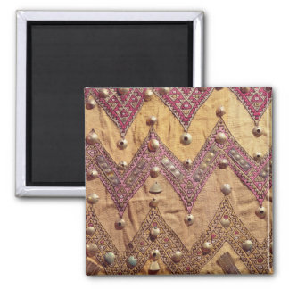 Section of embroidered fabric with gold plaques square magnet