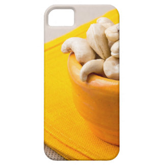 Selective focus on raw cashew nuts in a small cup case for the iPhone 5