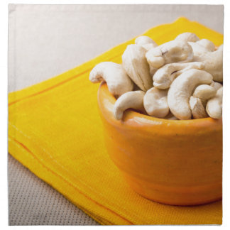 Selective focus on raw cashew nuts in a small cup napkin