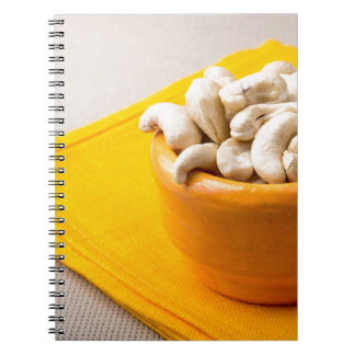 Selective focus on raw cashew nuts in a small cup notebook