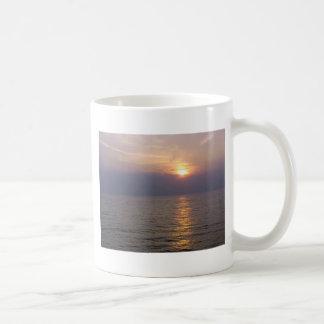 Setting sun over the sea mug