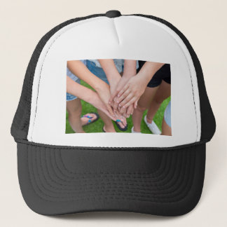 Several arms of girls with hands over each other trucker hat