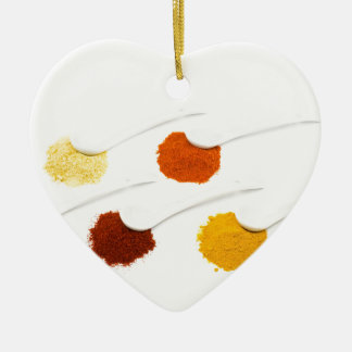 Several seasoning spices on porcelain spoons ceramic heart decoration