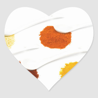 Several seasoning spices on porcelain spoons heart sticker