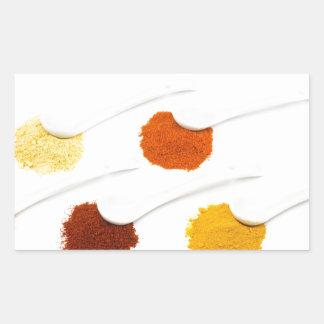 Several seasoning spices on porcelain spoons rectangular sticker