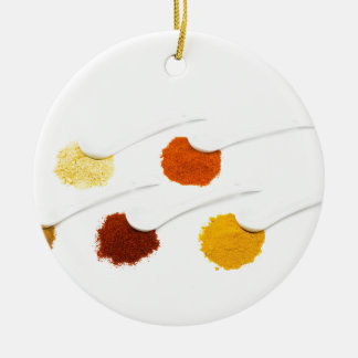Several seasoning spices on porcelain spoons round ceramic decoration