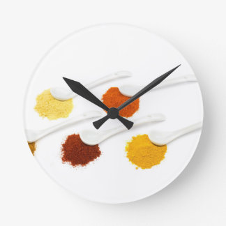 Several seasoning spices on porcelain spoons round clock