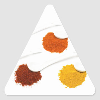 Several seasoning spices on porcelain spoons triangle sticker
