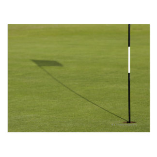 shadow of golf flag on golf course green post card