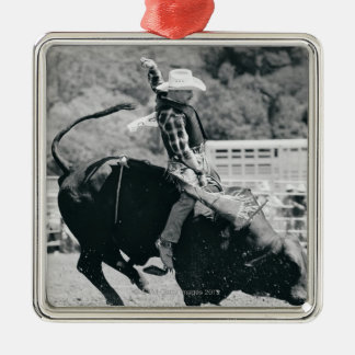 Side view of rider hanging on to bucking bull Silver-Colored square decoration