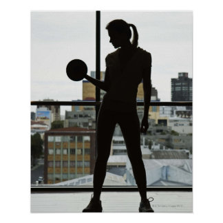 Silhouette of woman lifting weights at gym poster