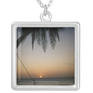 Silhuetted empty hammock at sunset silver plated necklace