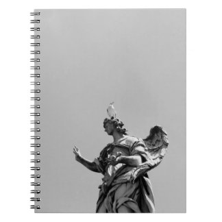 Simple, modern photo of seagull on top of statue notebook