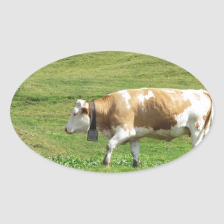 Single cow in an alpine pasture oval sticker