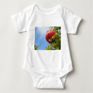 Single red pomegranate fruit on the tree in leaves baby bodysuit