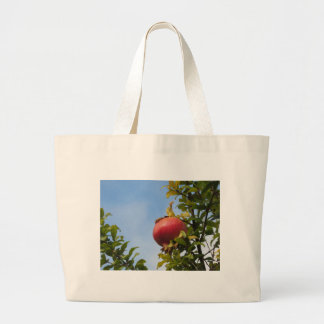 Single red pomegranate fruit on the tree in leaves large tote bag