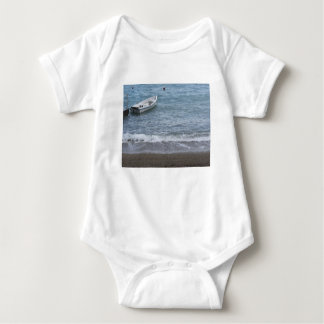 Single rowing boat moored in a harbor on the sea baby bodysuit