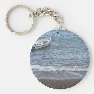 Single rowing boat moored in a harbor on the sea key ring