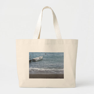 Single rowing boat moored in a harbor on the sea large tote bag