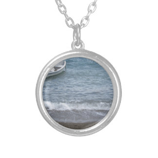 Single rowing boat moored in a harbor on the sea silver plated necklace